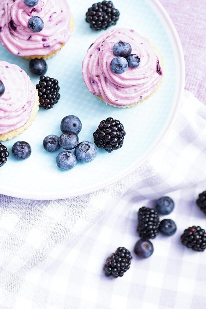 Dinkel-Cupcake mit Blaubeer Frosting auf Teller