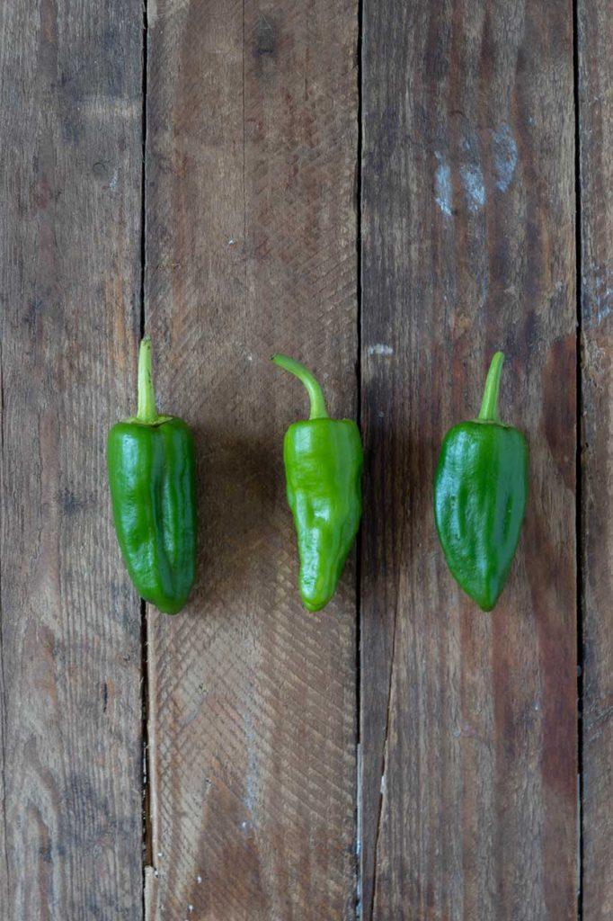 Grüne kleine Paprika auf dunkelm Holz