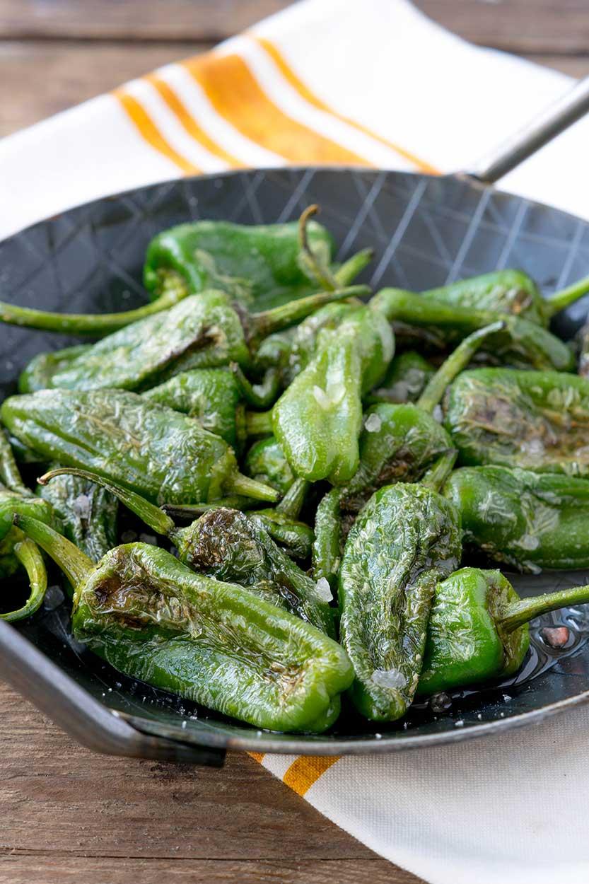 Grüne Paprika mit Salz in der Pfanne braten