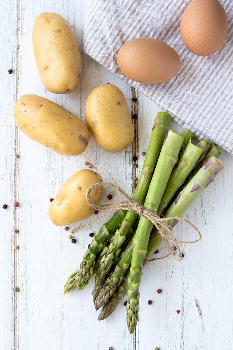 Grüner Spargel, Kartoffeln Eier auf weissem Holz