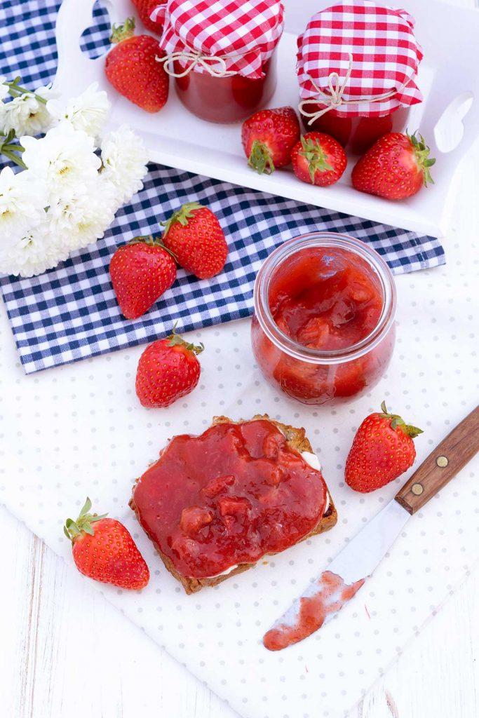 Erdbeermarmelade im Glas und auf Brot