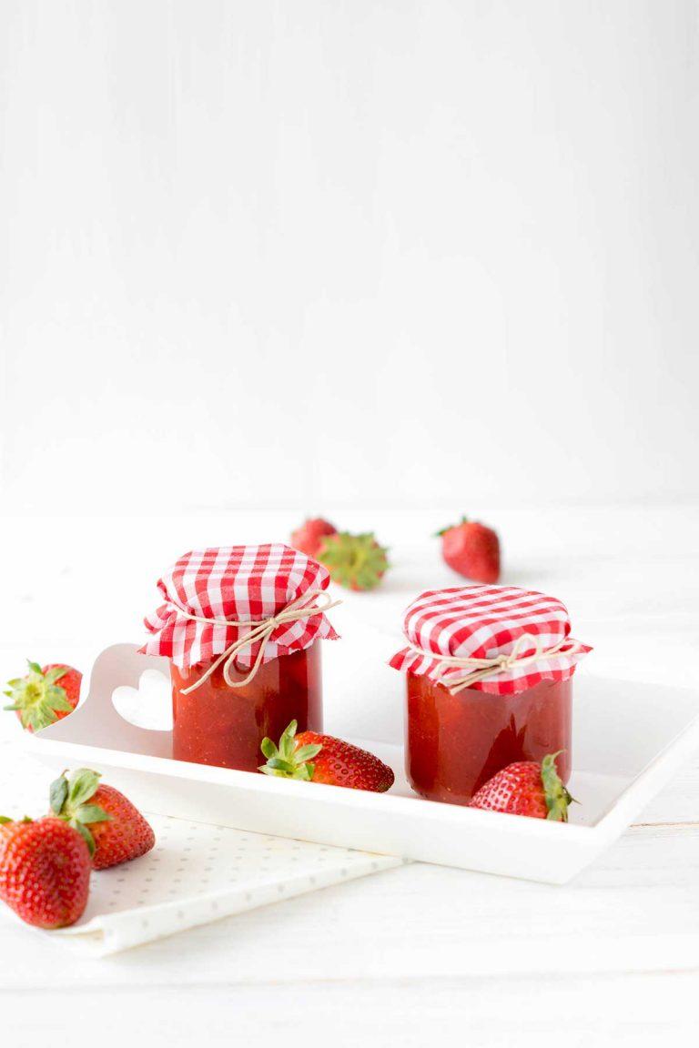 Erdbeermarmelade im Glas auf hellem Holz