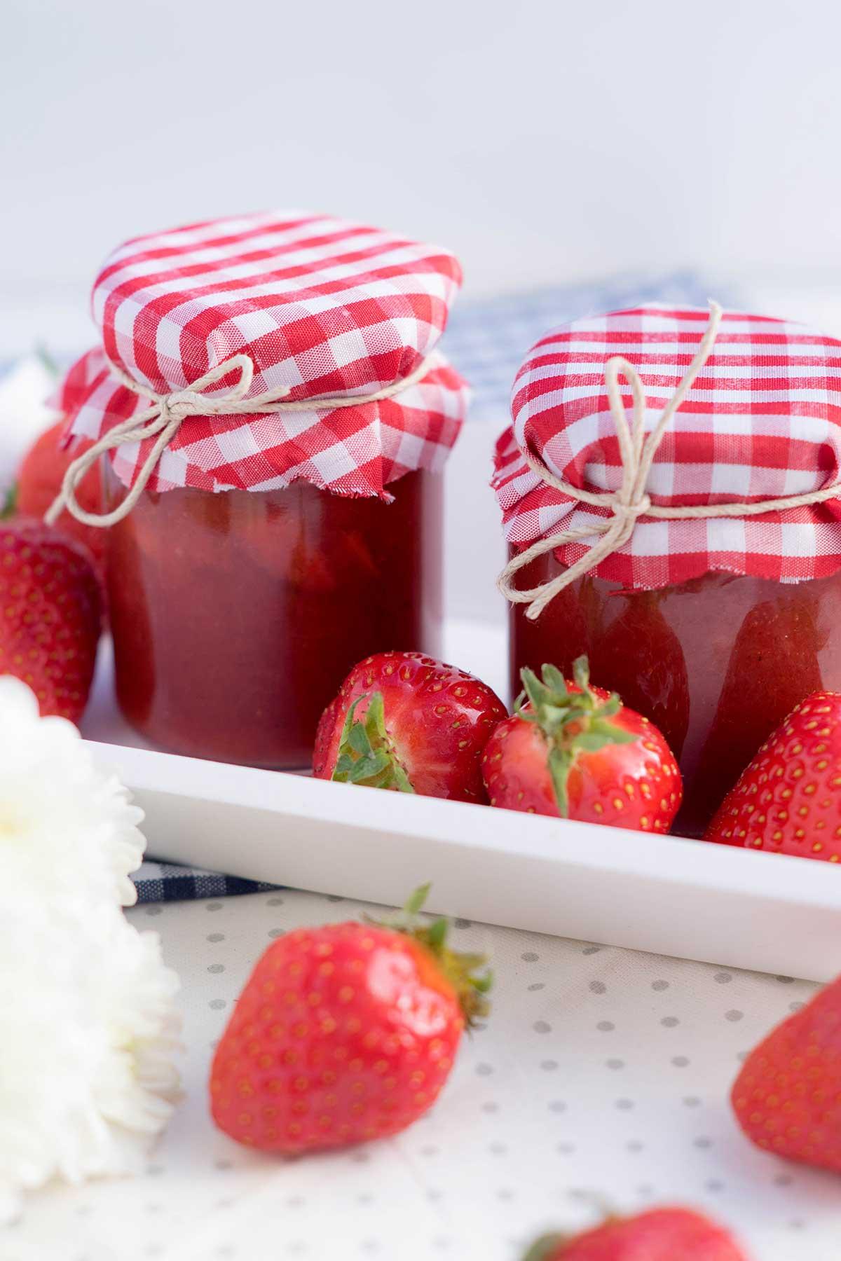 Erdbeermarmelade im Glas auf weißem Holz