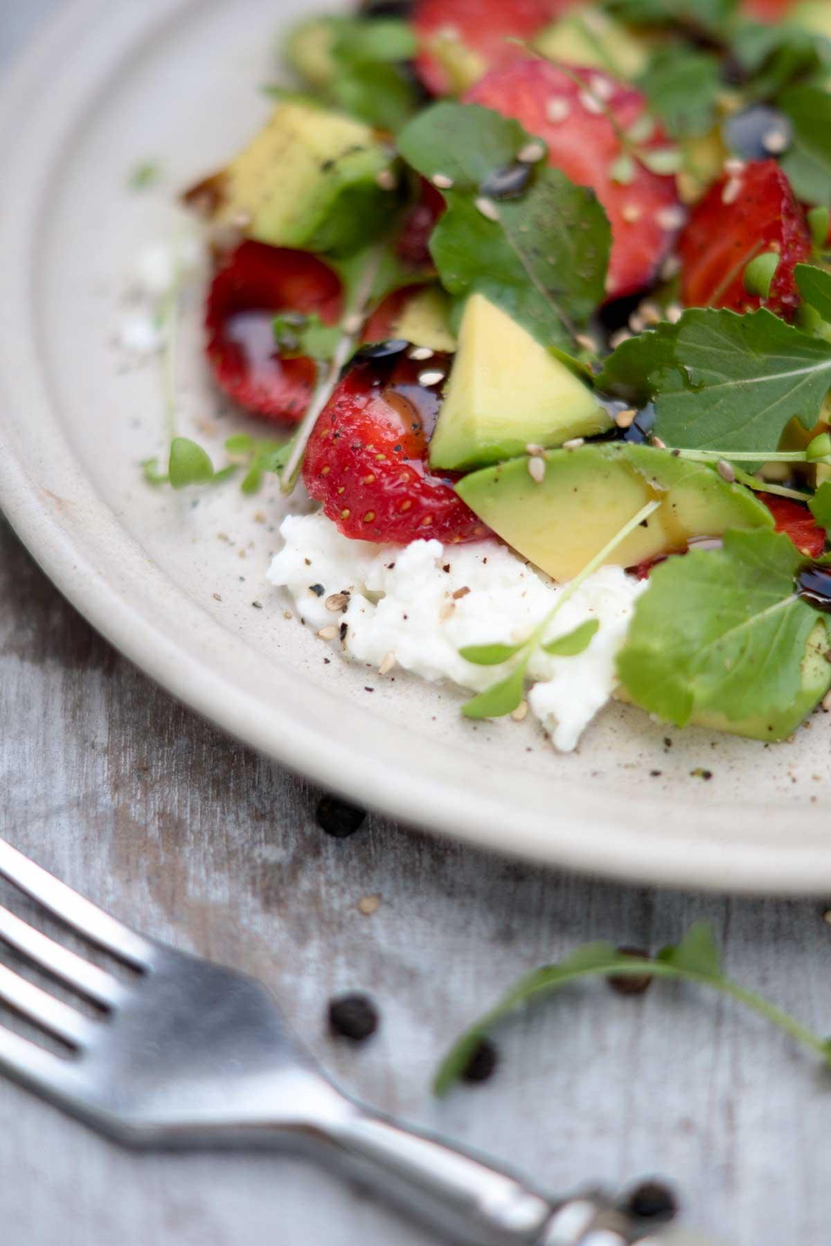 Bunter Salat mit Avocado und Erdbeeren auf Teller