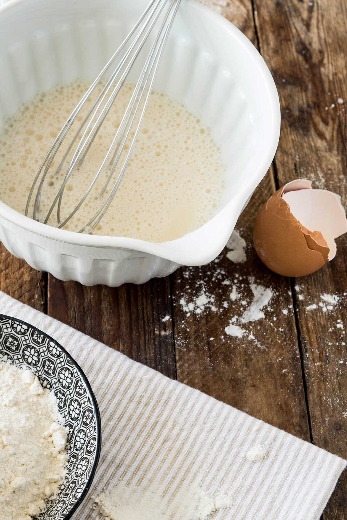 Schneebesen mit Eierkuchenteig in Schüssel
