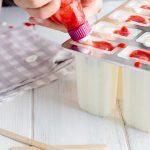 Spritzbeutel mit Erdbeerpüree in Eis spritzen
