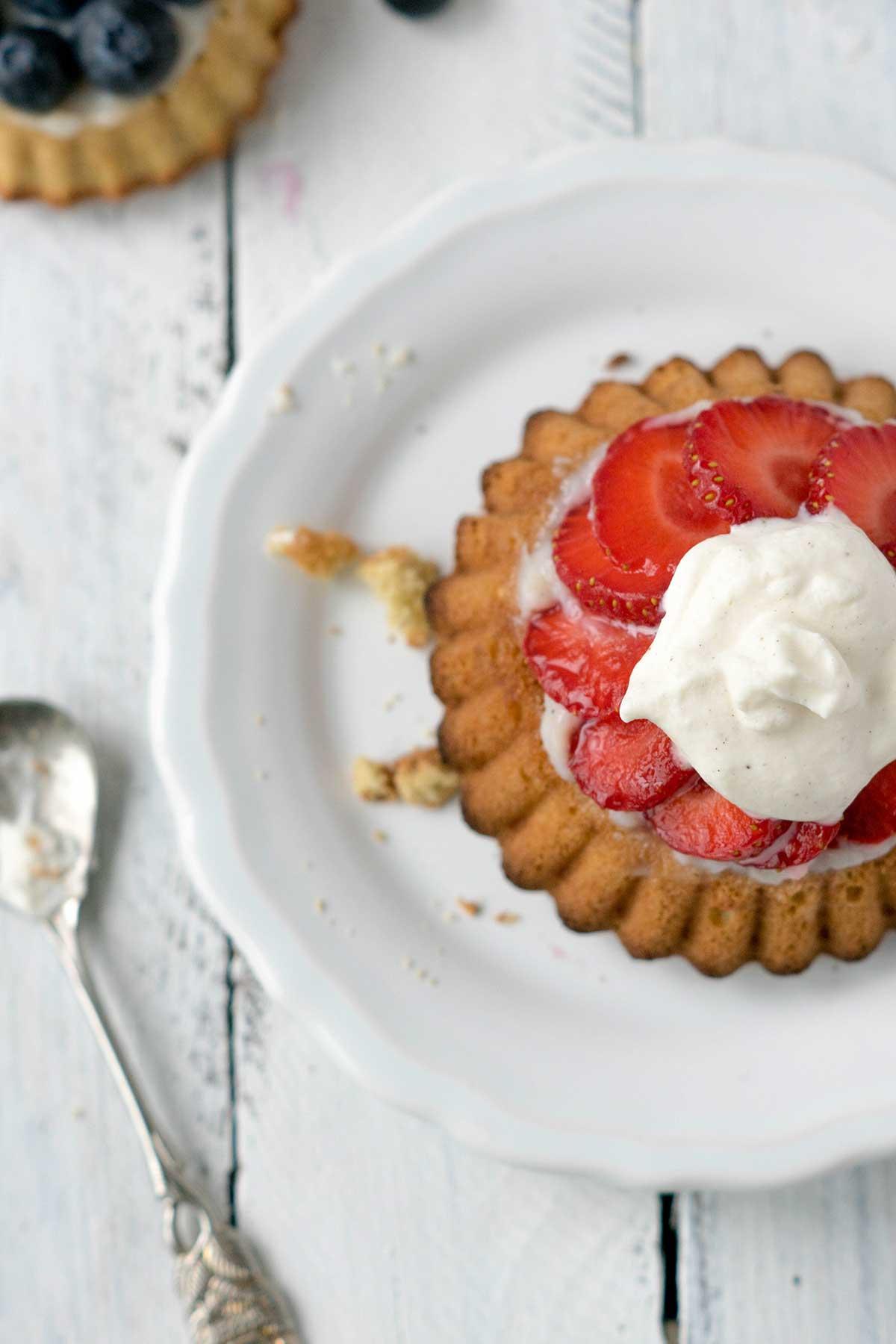 Tortelett mit Erdbeeren und Sahne auf einem Teller