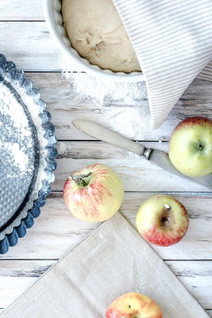 Blech, Äpfel und Teig auf einem Holztisch