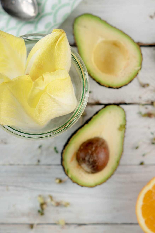 Avocado neben einem Glas mit Chicorée