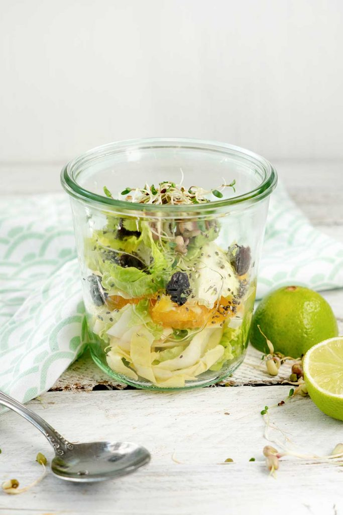 Salat im Glas auf weißem Holz