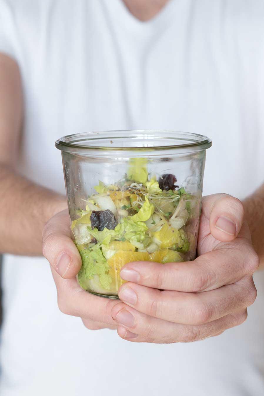 Salat im Glas in der Hand