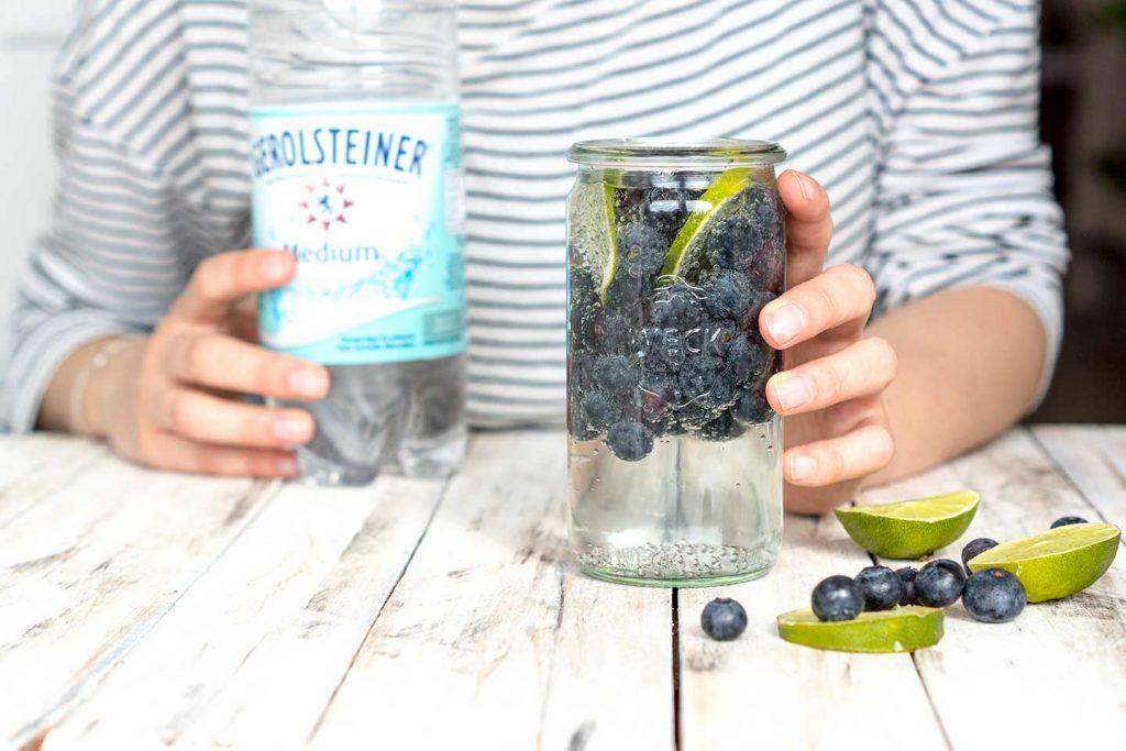 Zubereitung von infused Water mit Beeren und Limetten