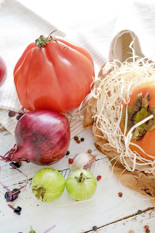 Tomate, Ziebel, Kaki auf Tisch