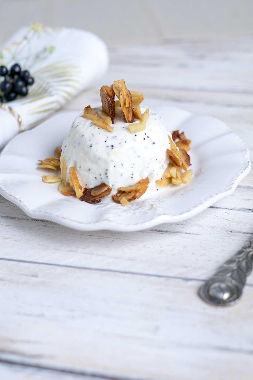 Orangencreme Dessert mit Mandelblättchen auf einem Teller