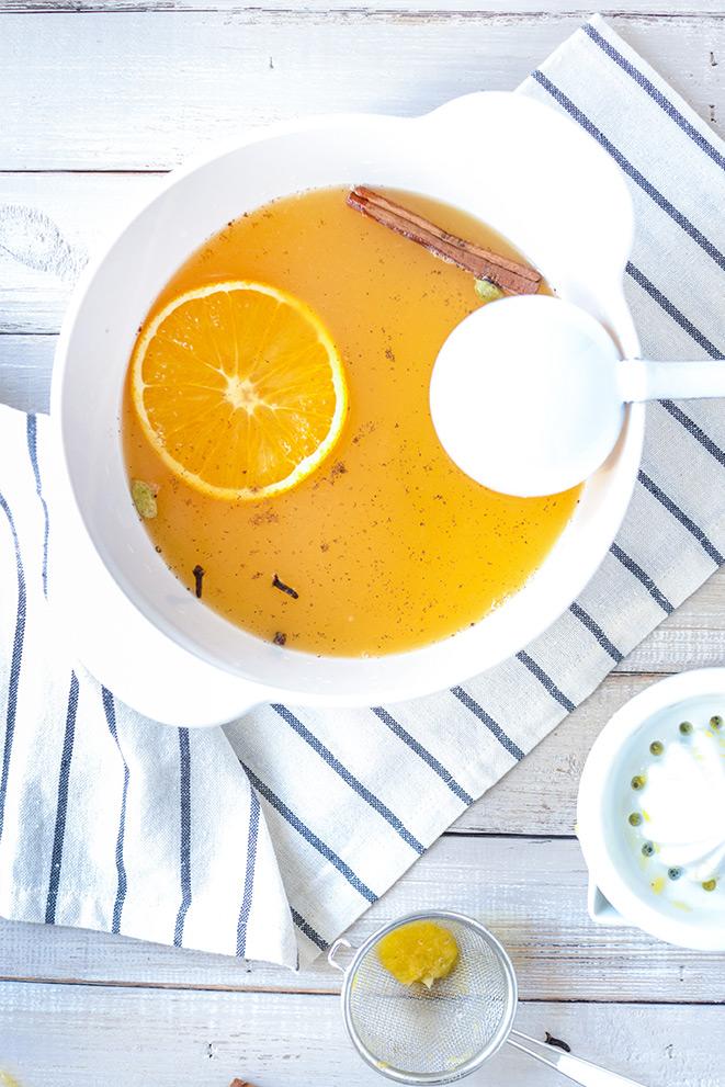 Orangenpunsch mit einer Kelle im Topf