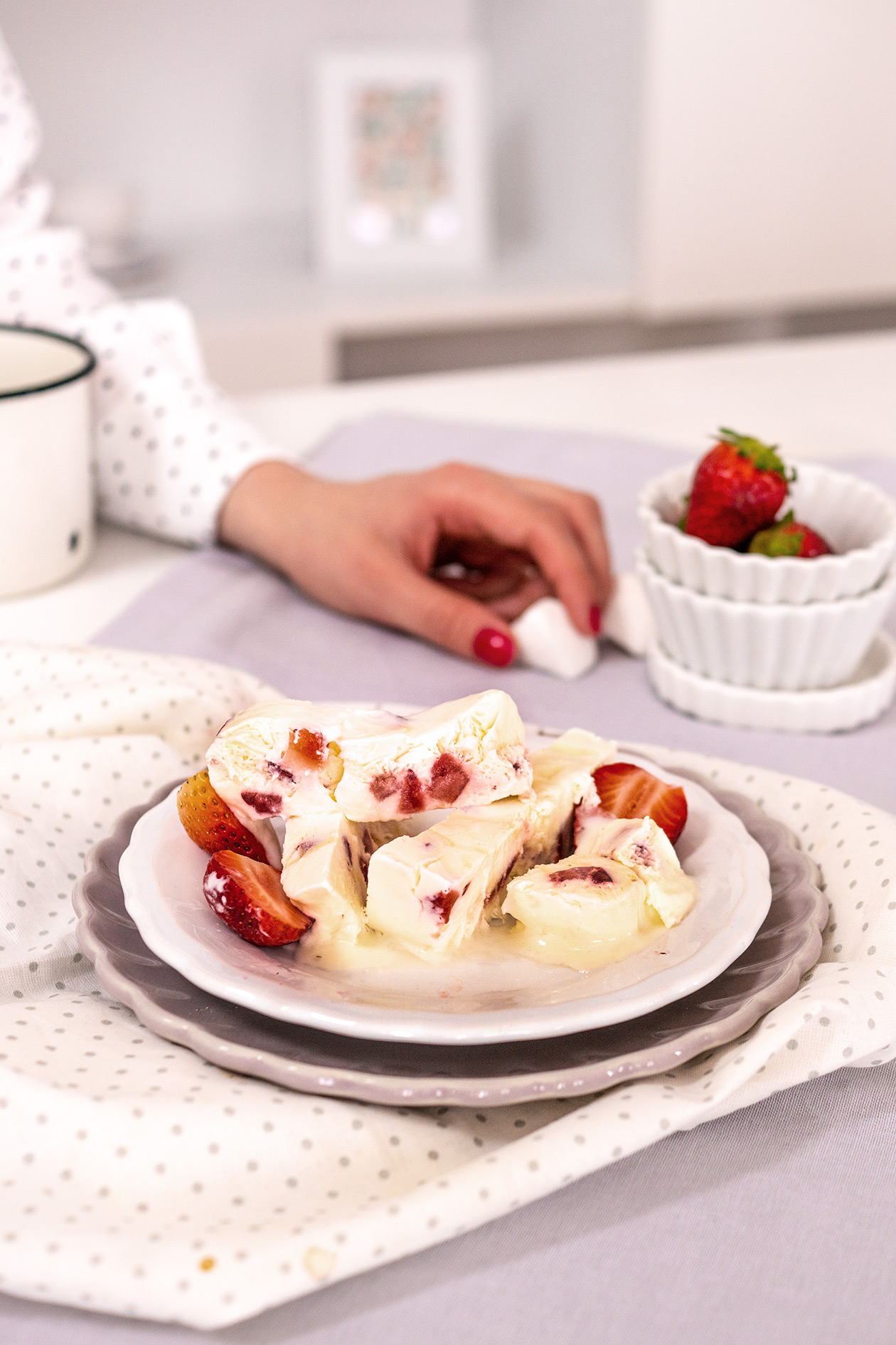 Eisdessert mit Erdbeeren und Hand im Hintergrund