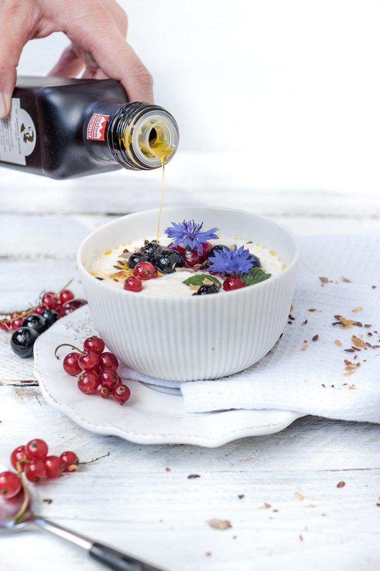 Leinöl wird in Joghurt mit Früchten gegossen