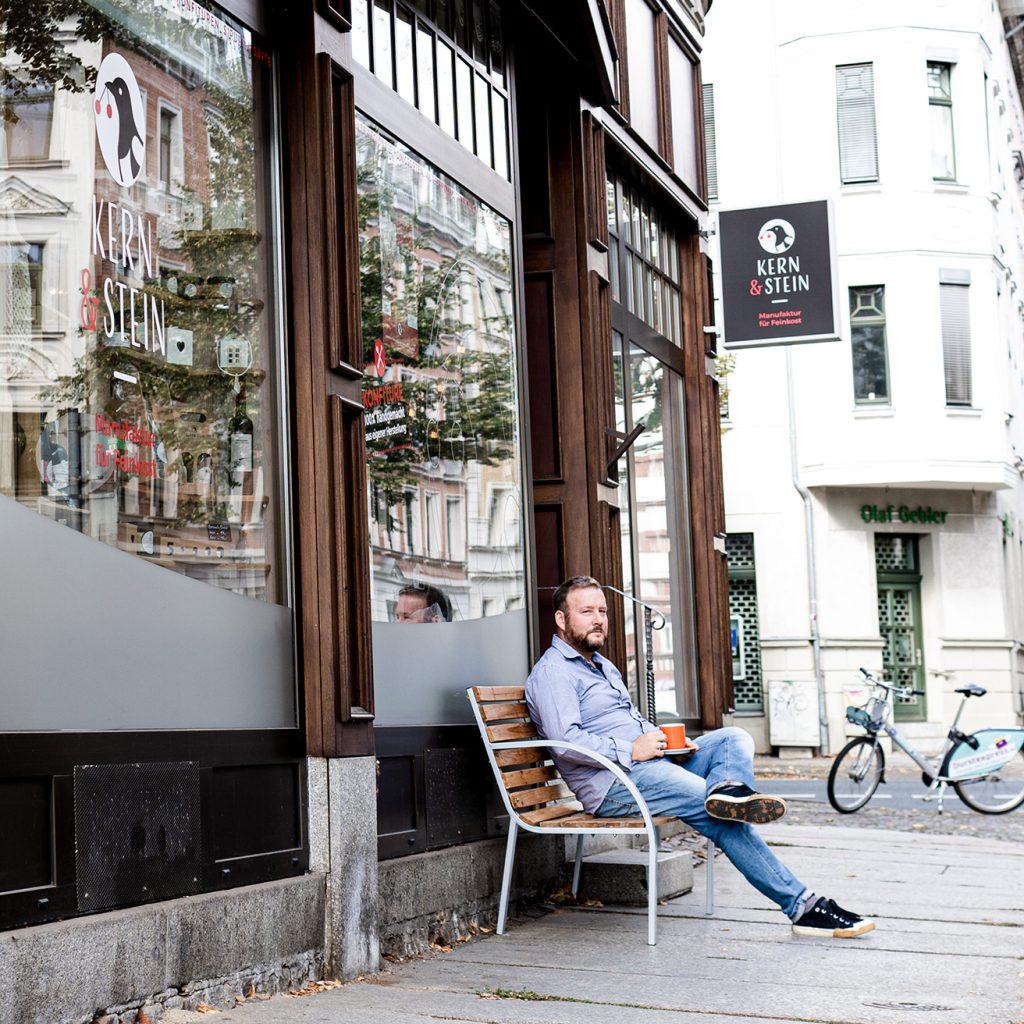 Mann mit Kaffee auf der Holzbank