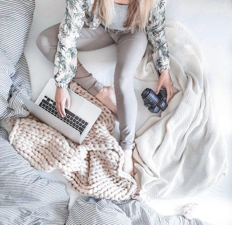 Frau sitzt im Bett und arbeitet am Laptop