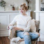 Frau sitzt auf einem Sessel und trinkt Kaffee