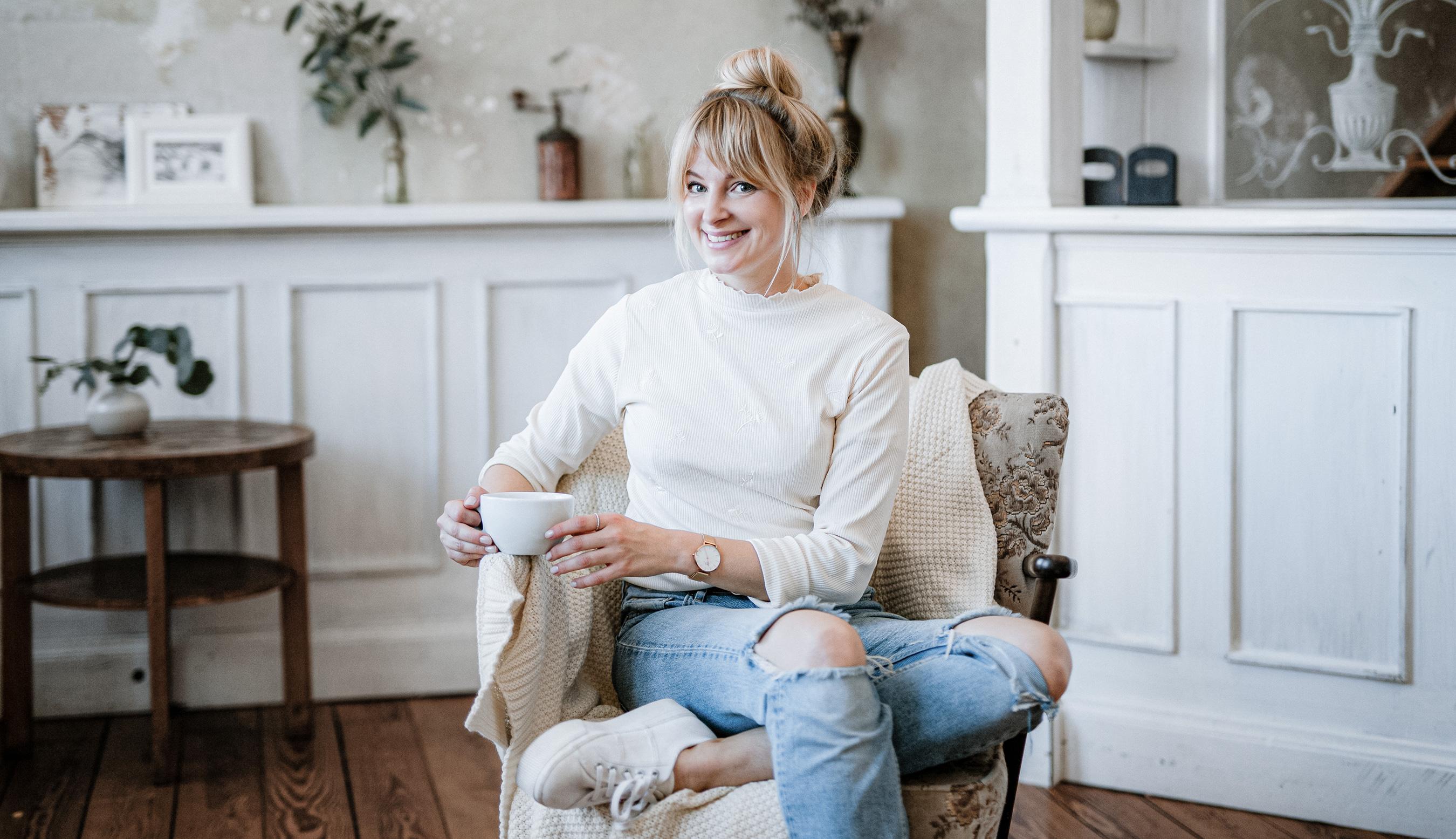 Frau auf Sessel lächelt und trinkt Kaffee