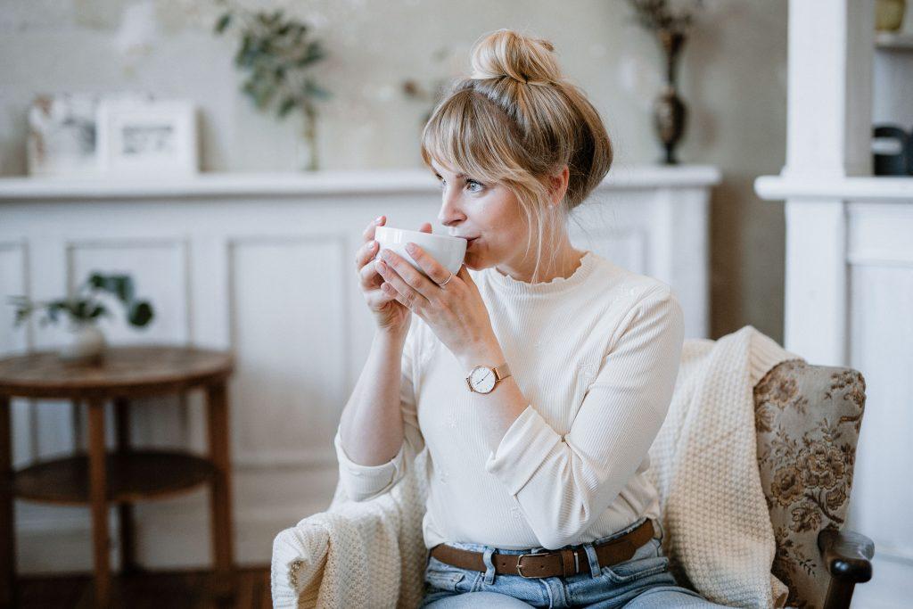Frau trinkt gemütlich Kaffee in einem Sessel