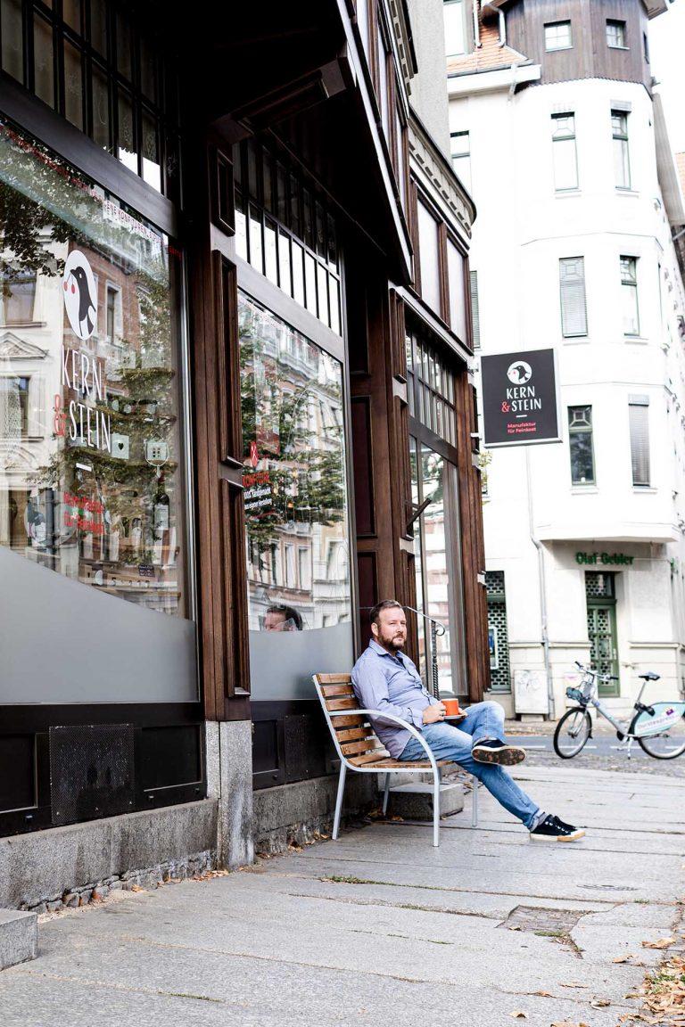 Mann mit Kaffee auf einer Holzbank