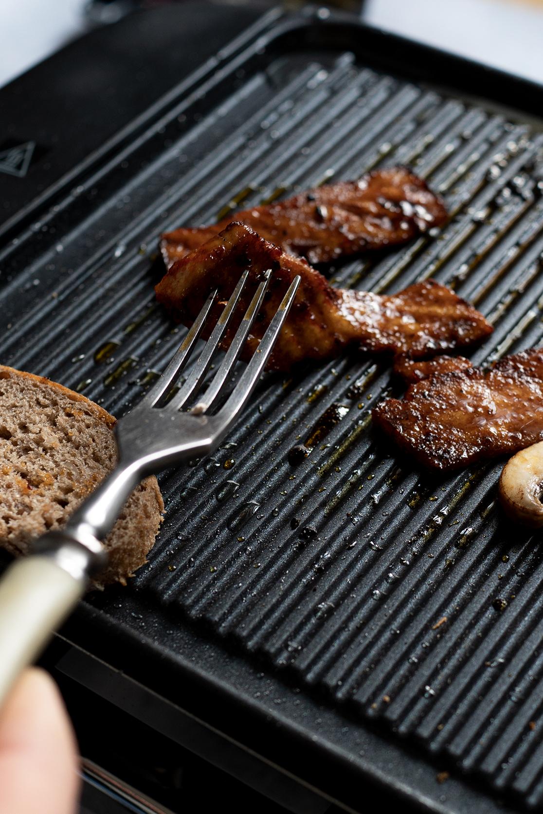 Tofu grillt auf dem Raclette und wird mit Gabel gewendet