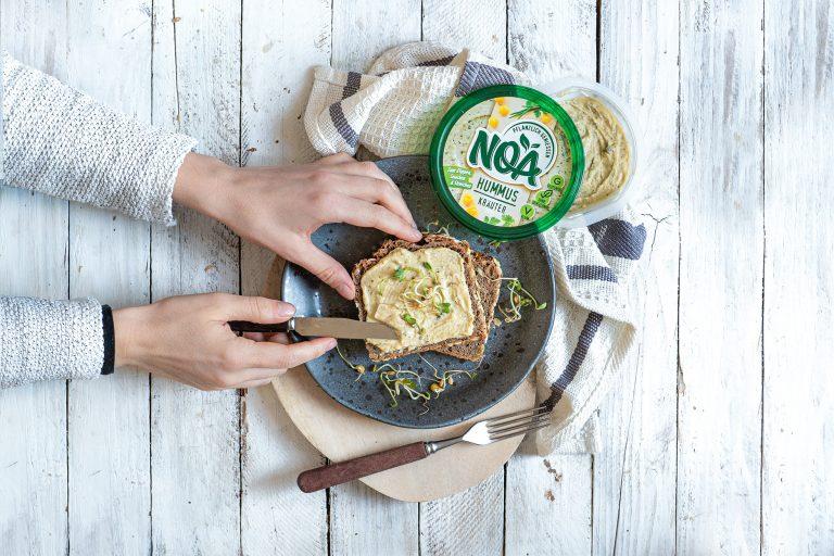Hände streichen Hummus auf Sandwich
