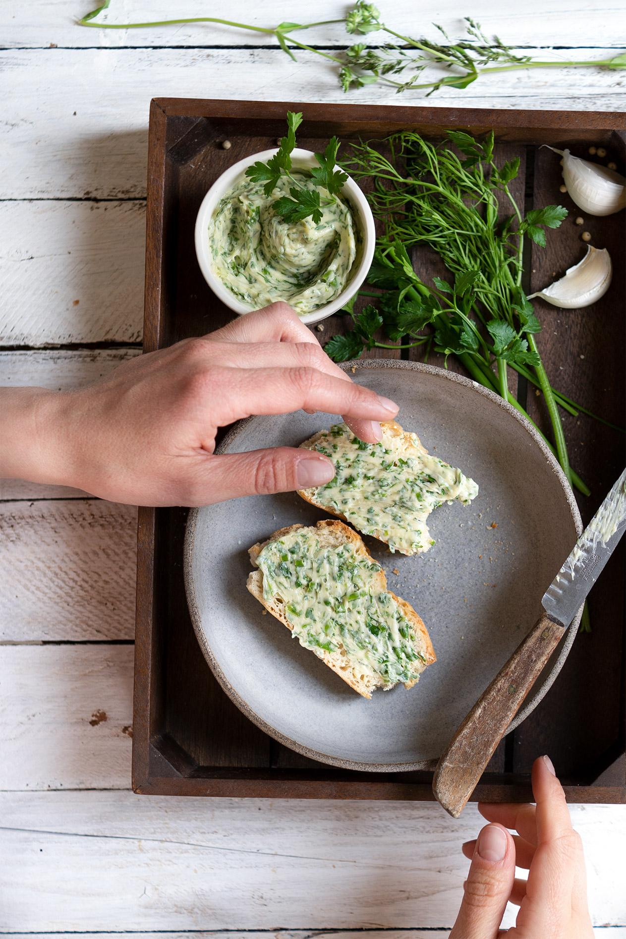 Hände schmieren ein Brot mit Kräuterbutter