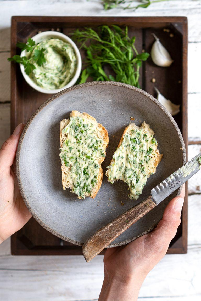 2 Scheiben Brot mit Kräuterbutter auf einem Teller